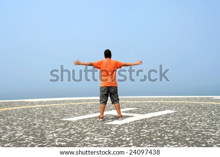 boy with arms wide open contemplating the ocean in foggy day - stock photo