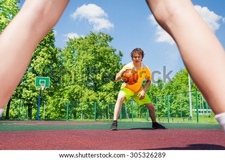 Boy with ball going to player at basketball - stock photo