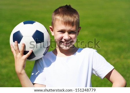 Boy with ball on the football field.
