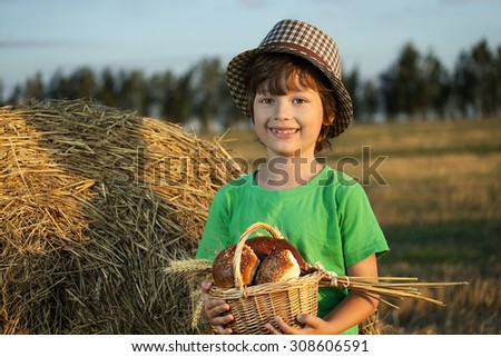 Boy with basket of buns in the background of haystacks in a field