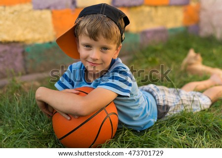 Boy with basketball sitting on green grass