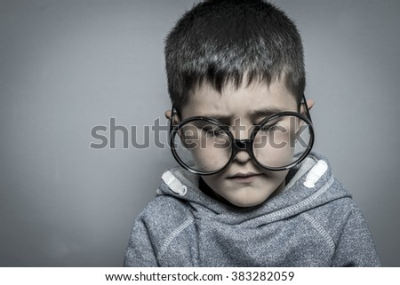 boy with big glasses very serious and thinking