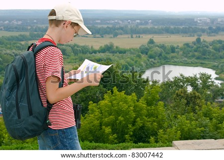 Boy with binoculars, backpack and map on a hike - stock photo