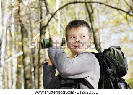 Boy with binoculars in autumn forest looking sideway - stock photo