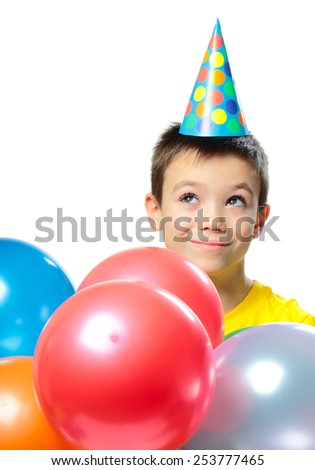 Boy with birthday cap and colorful balloons looking up  on white background - stock photo