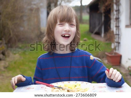 Boy with Blond Hair Eating Outdoors Smiling - stock photo