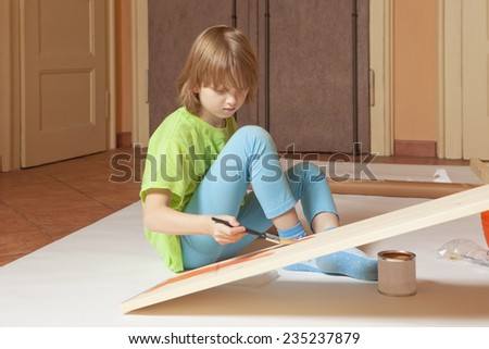 Boy with Blond Hair Painting a Board with Red Color - stock photo
