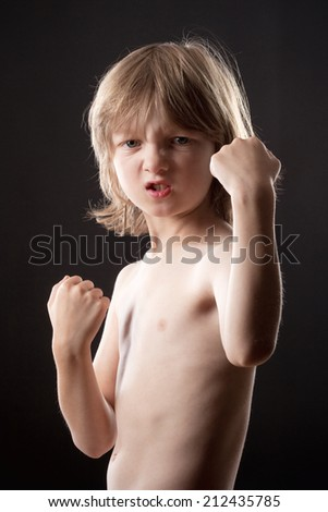 Boy with Blond Hair Striking a Fighting Pose - stock photo