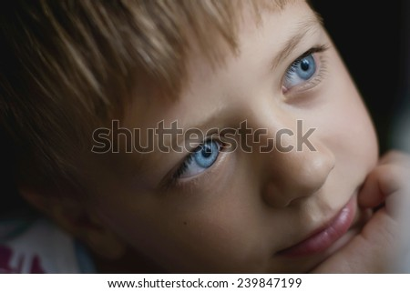 boy with blue eyes thinking while sitting by the window