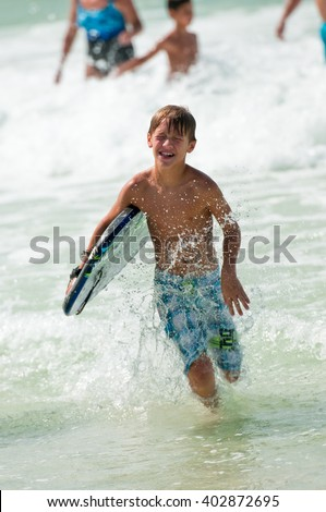 Boy with boogie board running in the ocean.