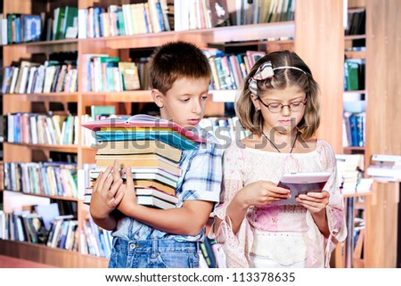 Boy with books pile and girl with e-reader - stock photo