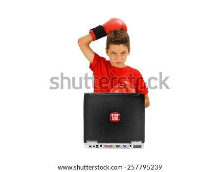 Boy with Boxing Gloves looking at camera with Stop Cyber Bullying Sticker Button on laptop isolated on white background - stock photo