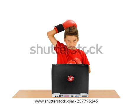 Boy with Boxing Gloves looking at camera with Stop Cyber Bullying Sticker Button on laptop on desk isolated on white background - stock photo