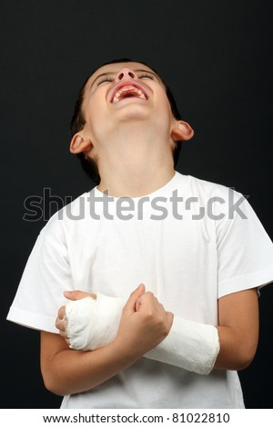 Boy with broken hand in cast, over black - stock photo