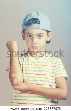 Boy with bruised elbow. Cross processed image - stock photo