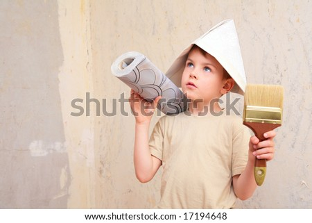 boy with brush and roll of wallpaper in papper hat - stock photo