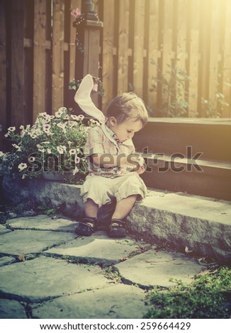 Boy with bunny ears resting on his shoulders spends a quiet moment for himself, and sits on a step peeling an egg he finds during an Easter hunt.  Filtered for a retro, vintage look. - stock photo