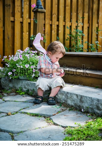 Boy with bunny ears resting on his shoulders spends a quiet moment for himself to sit on a step and peel an egg he finds during an Easter hunt in the spring season in a beautiful garden setting.  - stock photo