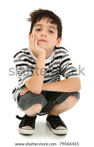 Boy with chin resting on hand with watching expression over white.
