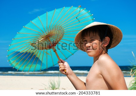 Boy with chinese umbrella on the beach