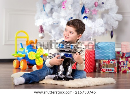 boy with Christmas gift, boy in festive costume near the Christmas tree - stock photo