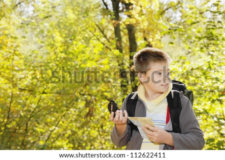 Boy with compass and map orienteering in forest looking sideways - stock photo