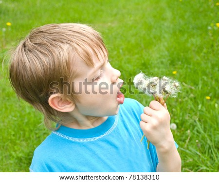 boy with dandelion outdoors at sunny summer day