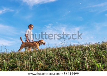 Boy with dog walk together on green hill - stock photo