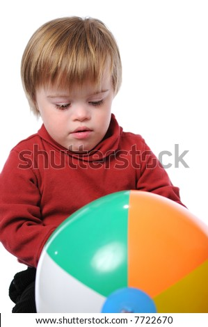 Boy with down syndrome playing with a beach ball - stock photo