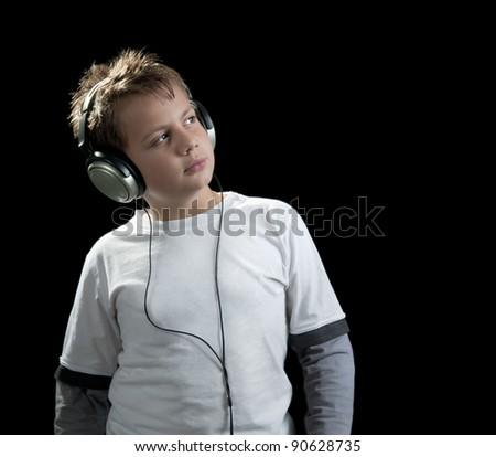 boy with earphones isolated on black - stock photo