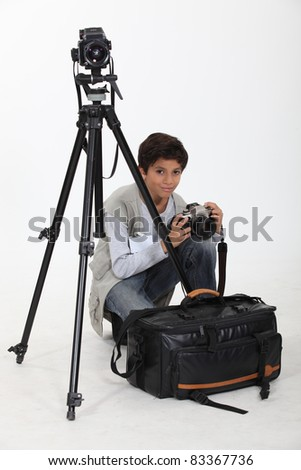 Boy with equipment of photographer - stock photo