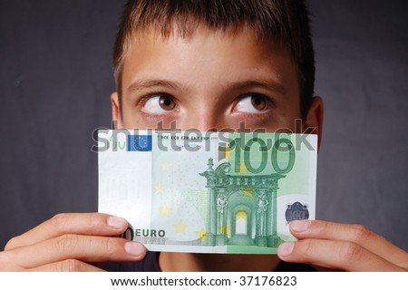 Boy with 100 euro banknote dreaming - stock photo