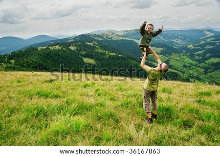 boy with father on mountain top - stock photo