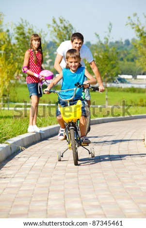 Boy with father riding bicycles - stock photo