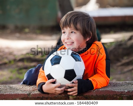 Boy with football soccer / shirt and ball in a park - stock photo