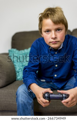 boy with gamepad in his hand, concentrating on his game - stock photo