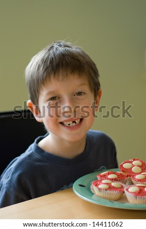 Boy with gap-tooth smile and cupcakes - stock photo
