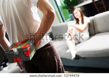Boy with gift and girl on sofa - stock photo