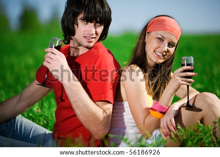 Boy with girl and with wineglasses on grass - stock photo