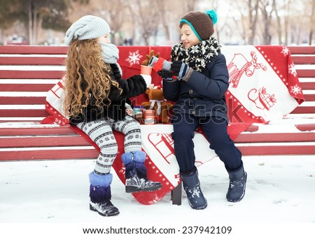 boy with girl drink coffee together in the winter on a bench in the park - stock photo