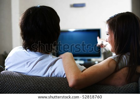 Boy with girl in front of TV - stock photo
