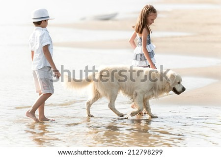 Boy with girl walking along the shore of the lake with the dog in a sunny summer day - stock photo