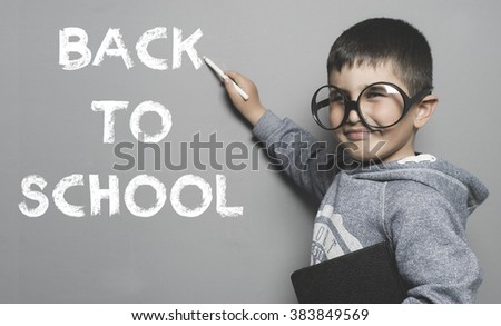 boy with glasses and funny gesture writing on the blackboard the text back to school
