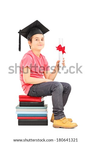 Boy with graduation hat sitting on stack of books and holding a diploma isolated on white background - stock photo