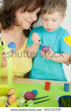 Boy with grandma doing the coloring eggs - stock photo