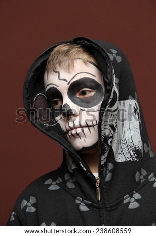 Boy with halloween zombie make up on brown - stock photo