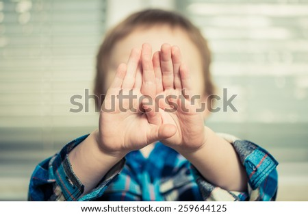 boy with hands in front of face