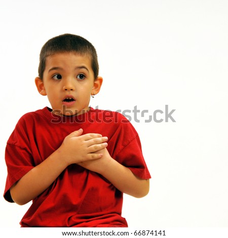 Boy with hands over heart, being frightened - stock photo