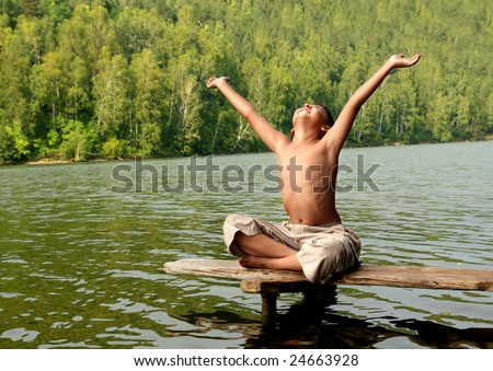 boy with hands up on stage in lake - stock photo