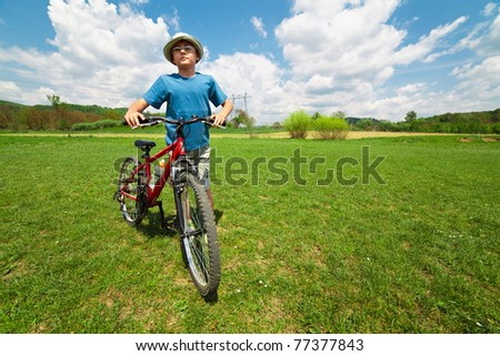 Boy with hat and his bicycle on a grass field - stock photo